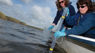 Researchers Heike Sederoff (left) and JoAnn Burkholder take water samples from Falls Lake. PHOTO BY ROGER WINSTEAD