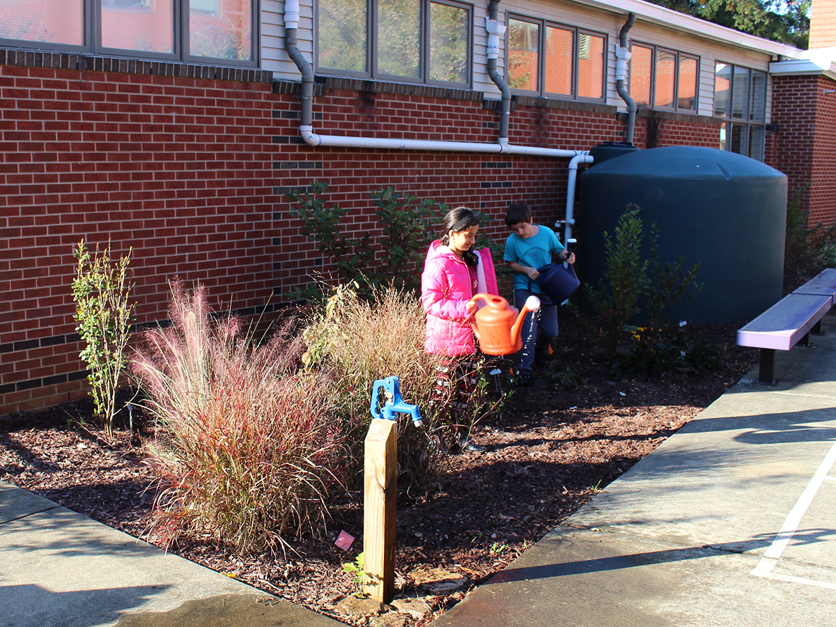 student watering flowers with collected rainwater