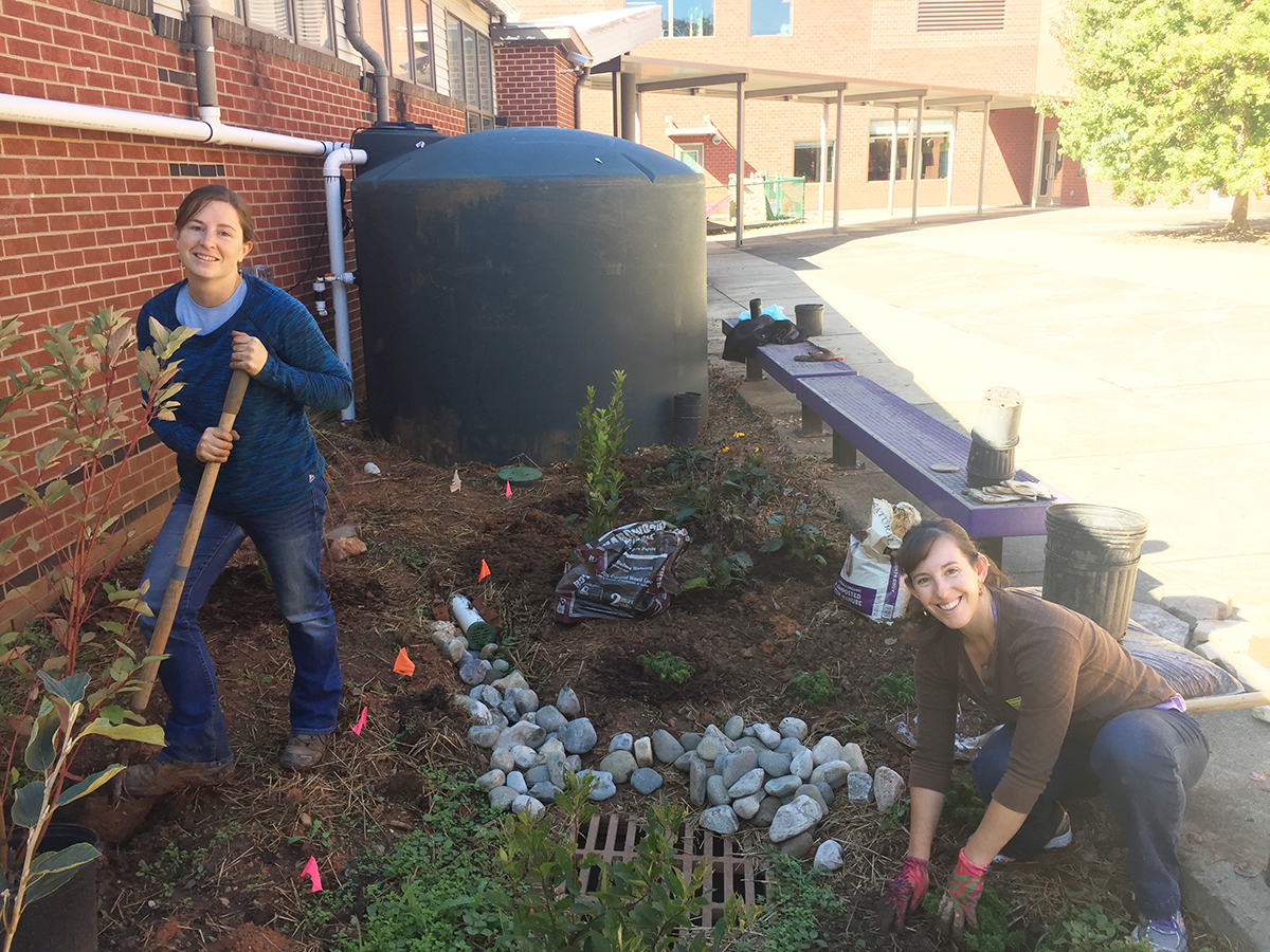 North Carolina Sea Grant's Jane Harrison and Anna Martin of Sea Grant and WRRI help plant native plants next to the Kingswood Elementary School rainwater cistern.