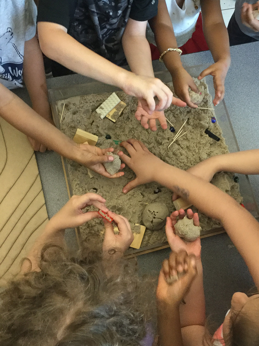 Young children play with sand in a watershed model at the Spring STEM Fair at Kingswood Elementary School.