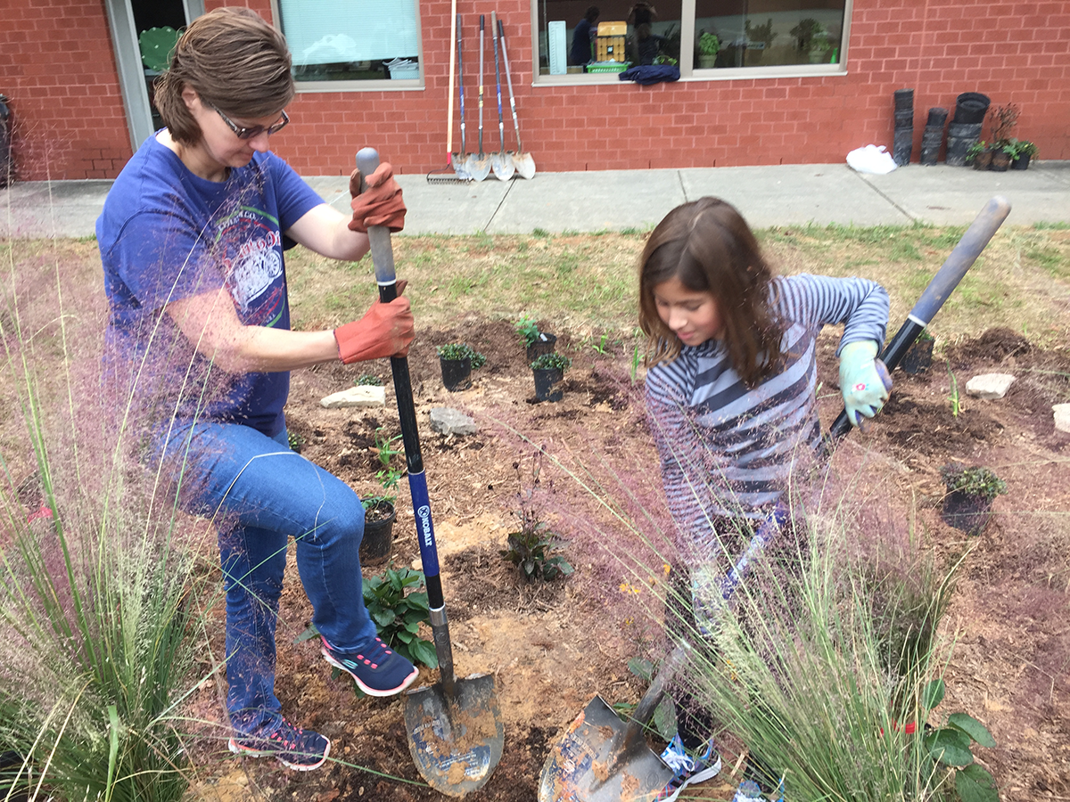 Kingswood parent and student dig holes for native plants in the school's rain garden
